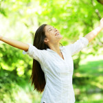 Young woman meditating with open arms standing in fresh spring g