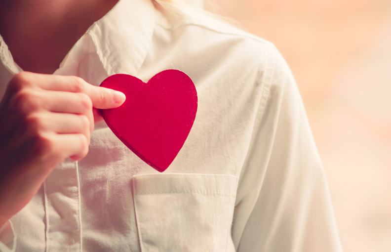 Heart shape love symbol in woman hands with white shirt pocket V